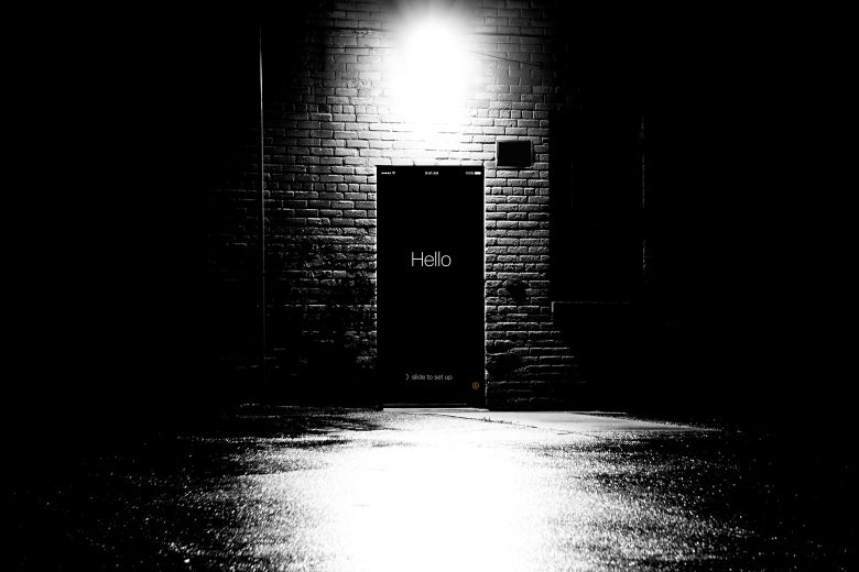 A dark door in a back alley with the Hello intro page of an iPhone.