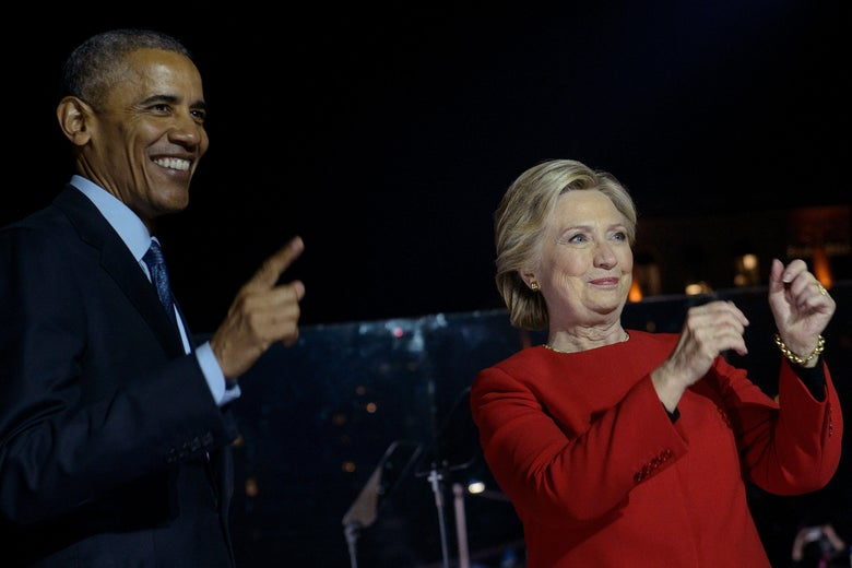 On a campaign rally stage, Obama smiles and points to the crowd while Hillary Clinton gestures with her hands.