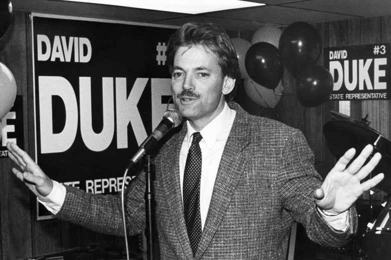 David Duke at a microphone in a suit and tie with campaign signs and balloons behind him