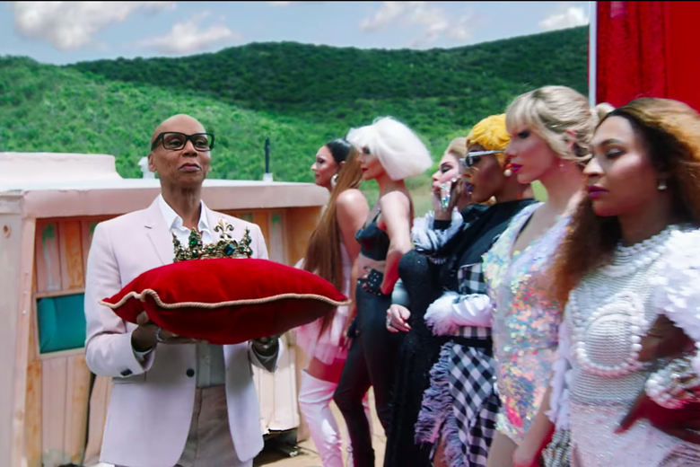 RuPaul tempts a line of drag queens with a crown.