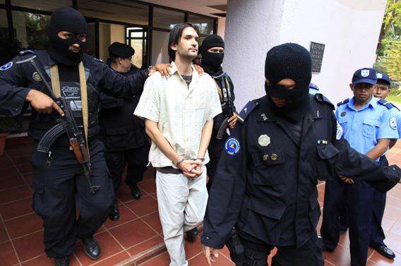 Eric Justin Toth of the U.S. is escorted after a presentation to the media at police headquarters building in Managua April 22, 2013.