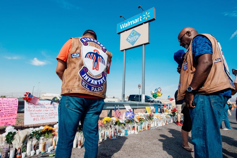 People in motorcycle gear bow their heads in prayer before a memorial of flowers and signs of support for the shooting victims.