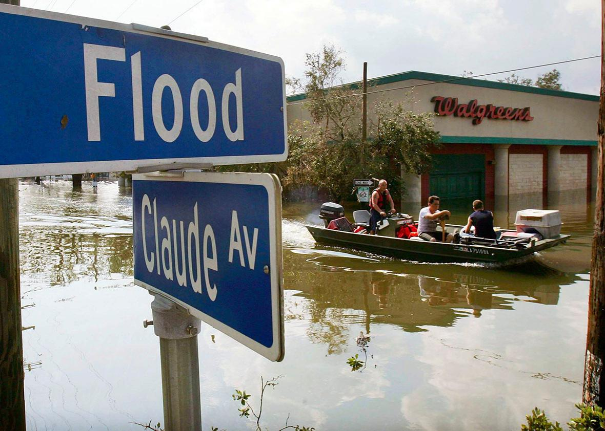 Men ride in a boat in high water past Flood Street after Hurrica