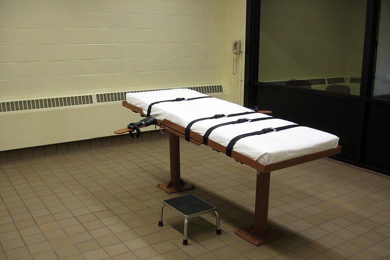 A cot with straps in an execution chamber.