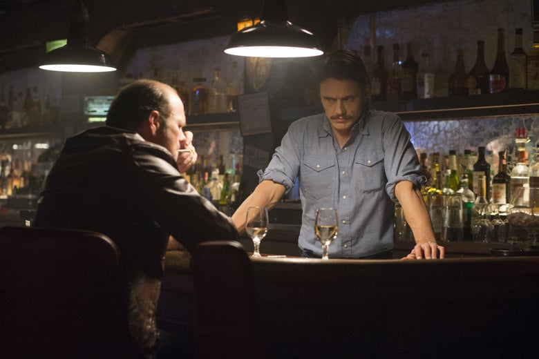 Chris Bauer sits at a bar, while James Franco, with a prominent mustache, stands behind it.