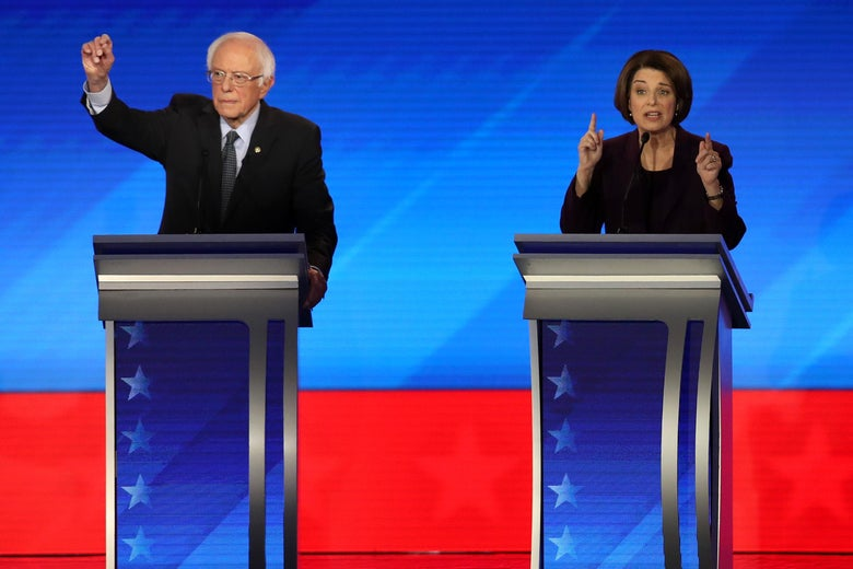 Bernie Sanders and Amy Klobuchar stand at their respective podiums while gesturing with their hands.