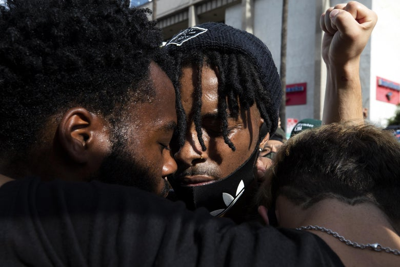 Two black protesters closing their eyes and putting their heads together as a white fist is held up in the shot.