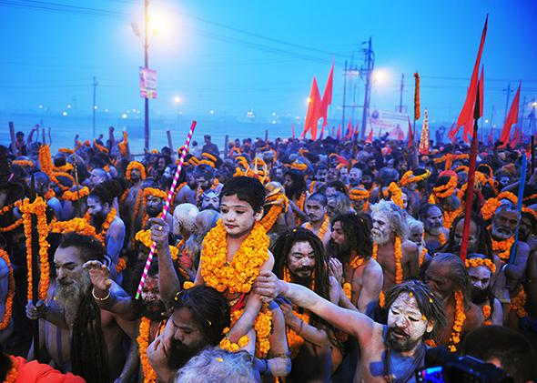 Hindu holy men carry a child adorned with marigold flowers on their shoulders as they march toward the Sangham during the Kumbh Mela on Jan. 14, 2013, in Allahabad, India.