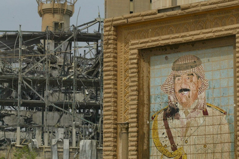 A damaged mural of Iraq's ousted leader Saddam Hussein in a military outfit, next to a destroyed building in Baghdad
