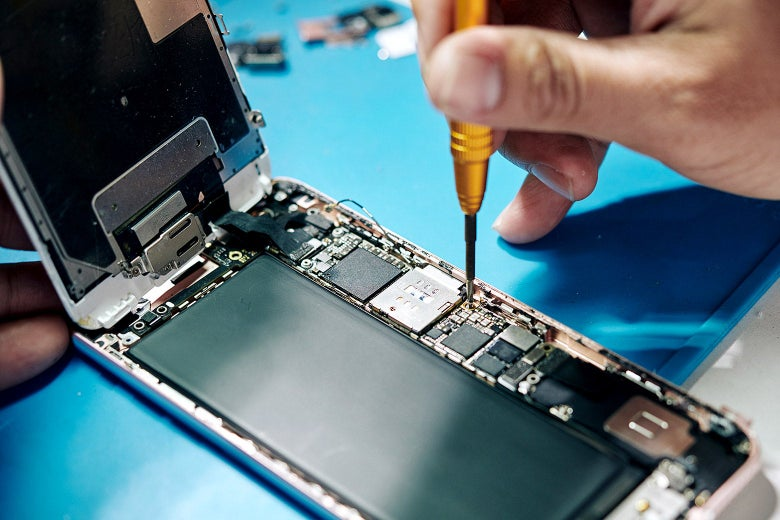 Someone fixing an iPhone with a screwdriver.