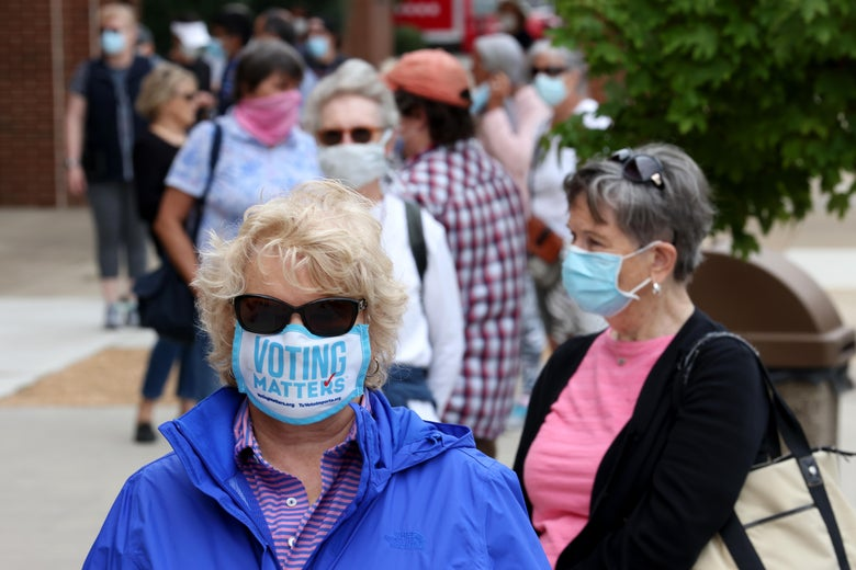 A line of people wearing masks