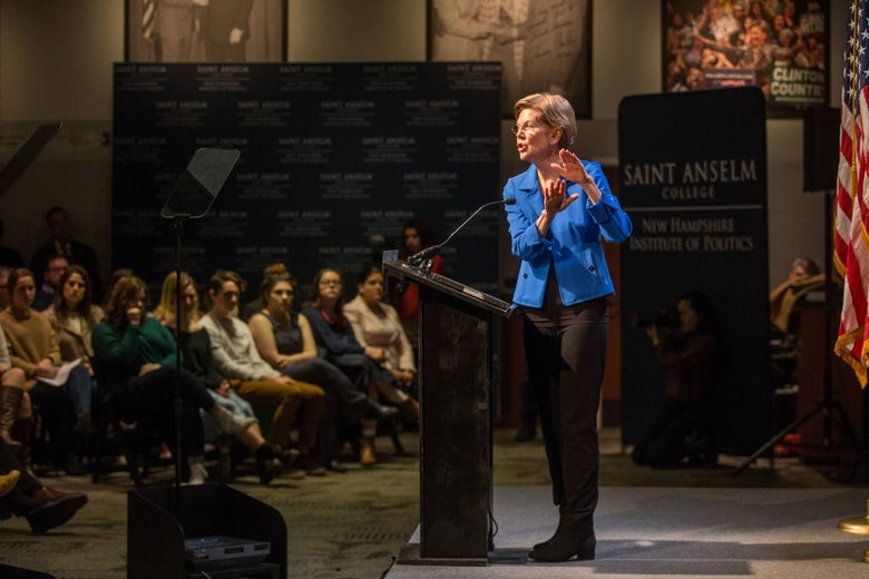 Warren, seen from the side as she gestures with both hands and speaks from a lectern to a seated group of college students.