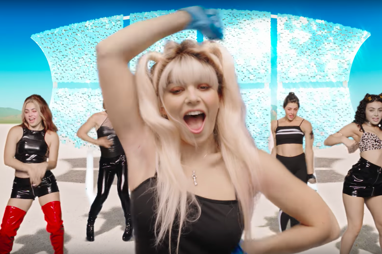 Charlie XCX with two blond high ponytails dancing in front of back-up dancers