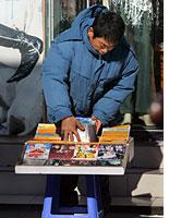 A street vendor in China selling pirated discs         Click image to expand.