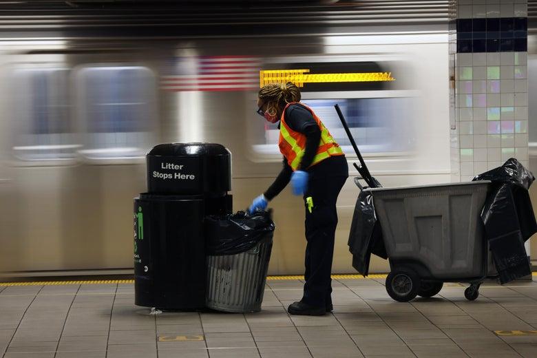 A woman empties trash on a subway platform.