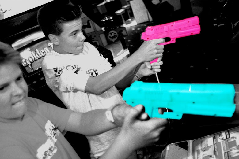 Kids play with toy guns at arcade.