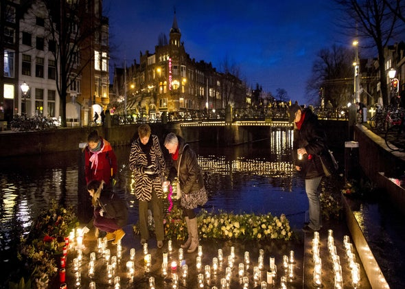 People place candles at the Homomonument in Amsterdam  during the opening ceremony of the Olympic Games in Sochi on Feb. 7.