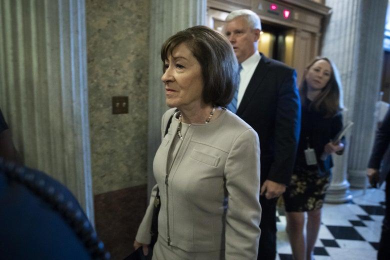 Susan Collins walking in a Senate hallway.