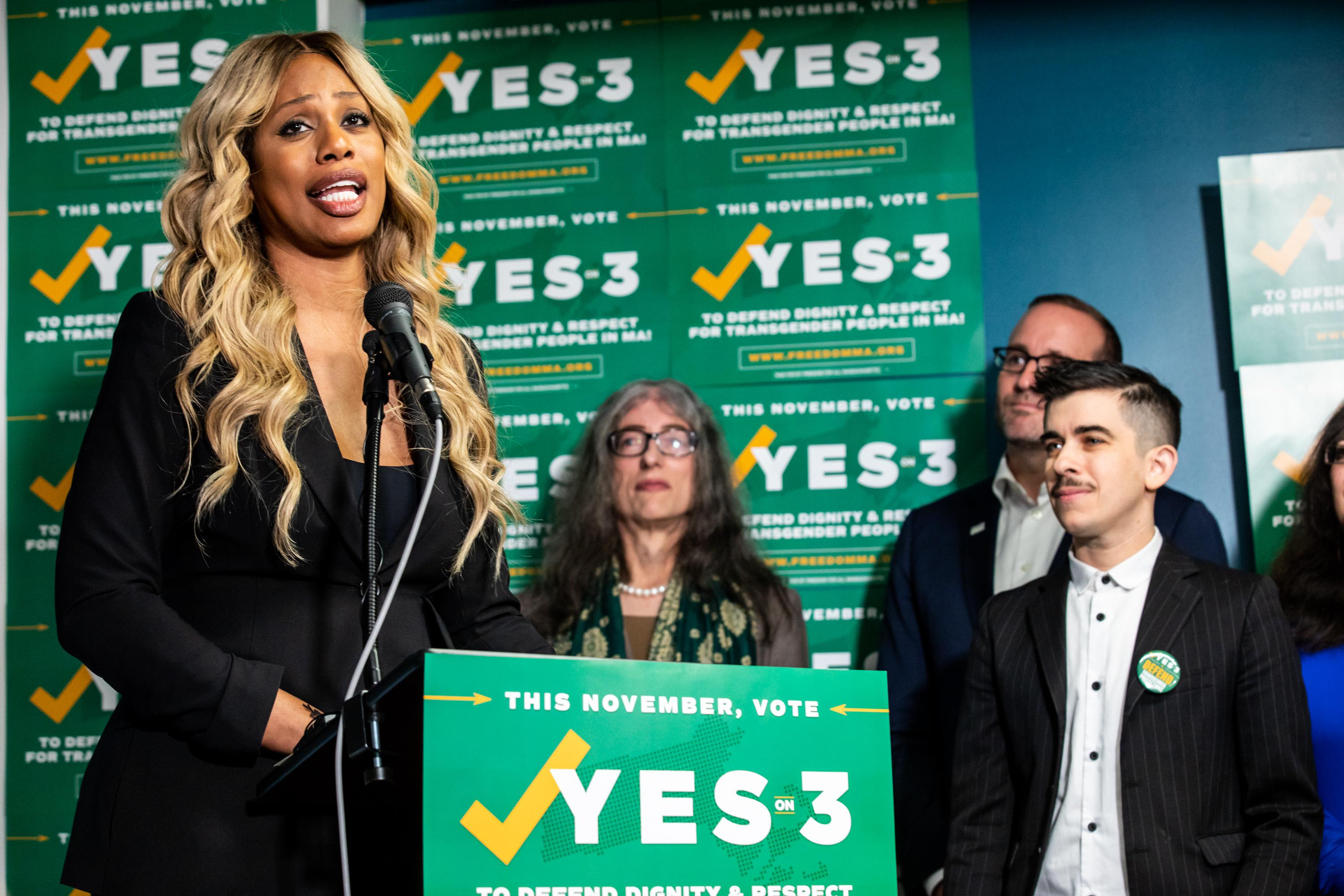 Laverne Cox speaks at a lectern with other activists.