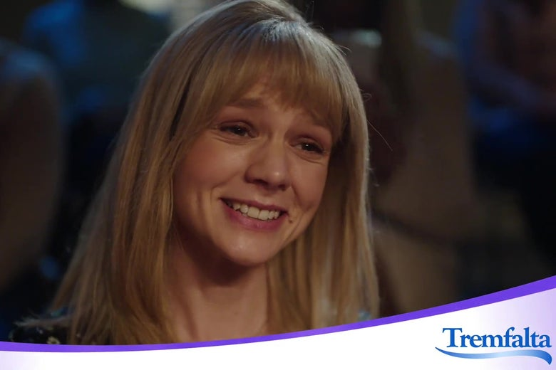 """Carey Mulligan, in a blonde, long wig, smiles at the camera. Below her, a banner reads """"Tremfaulta,"""" the name of the drug she is advertising."""