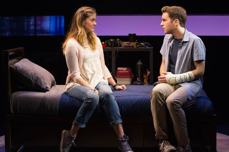 A blonde girl and a boy with brown hair sit on a bed, facing each other. The boy has a blue shirt, khaki pants, and gray sneakers; he also has a cast on his arm. The girl wears a pink shirt, blue jeans, and black sneakers. She miles at him while he pleads with her.