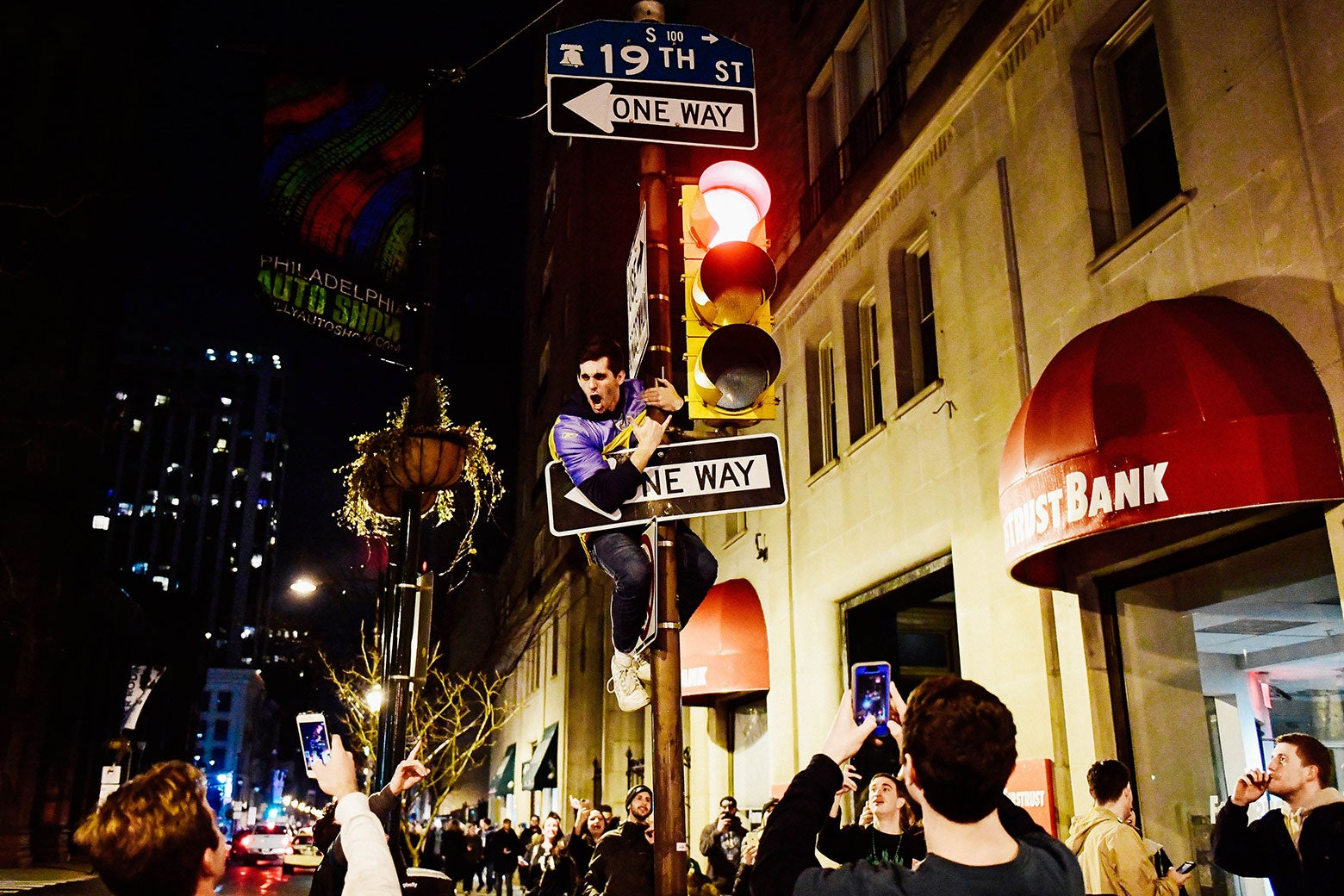 A fan climbs a pole reacting to Super Bowl LII on Walnut Street near City Hall on Sunday in downtown Philadelphia.
