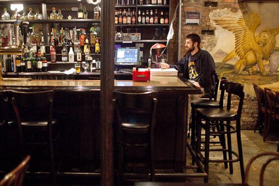A man drinks at a bar in the East Village of New York.