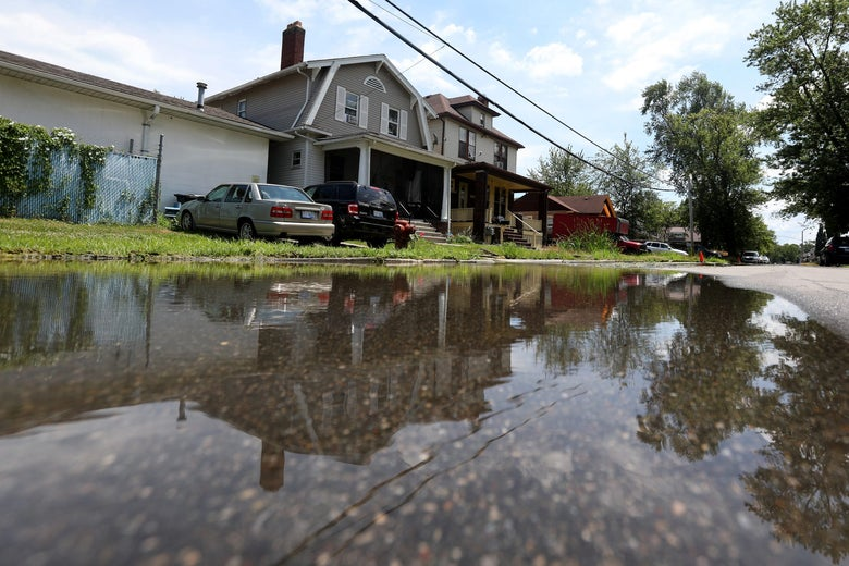 A partially flooded street in front of a house