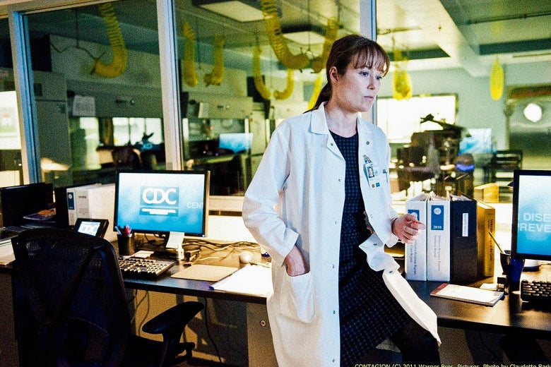 """A white-coated female scientist is seen a laboratory. A computer behind her reads """"CDC."""""""