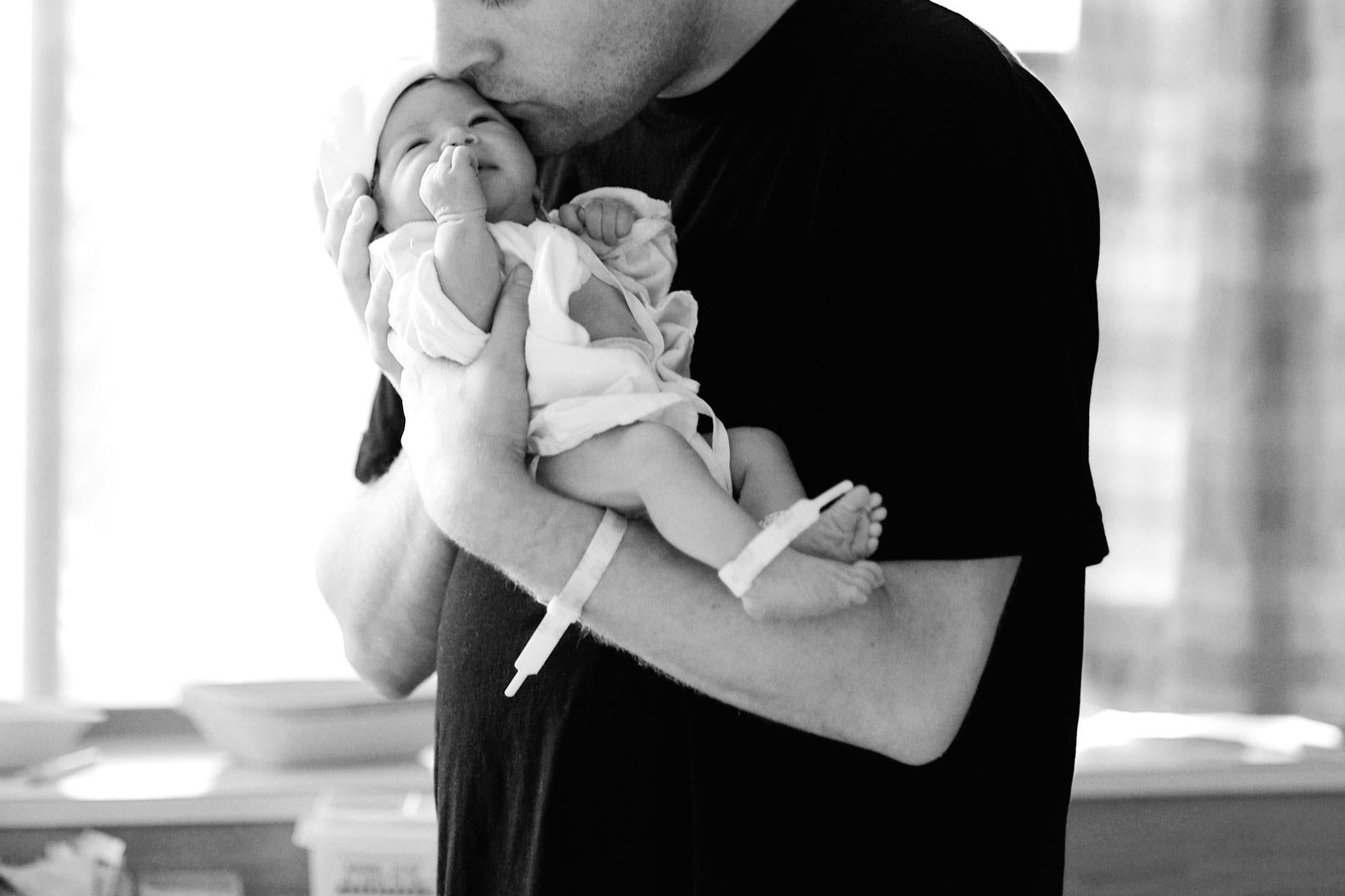Black-and-white stock photo of a father in the hospital holding a newborn.