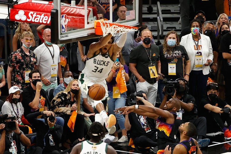 Giannis dunks on the side of the hoop with mouth agape and legs flying as Jrue Holiday, Chris Paul, Mikal Bridges, and Suns fans look on.