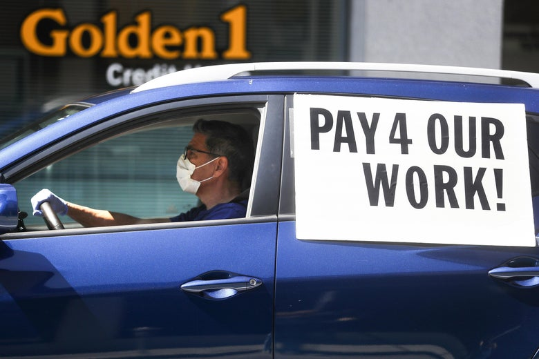 "A driver wearing a face mask and gloves, in a car with a sign that says ""Pay 4 Our Work!"""
