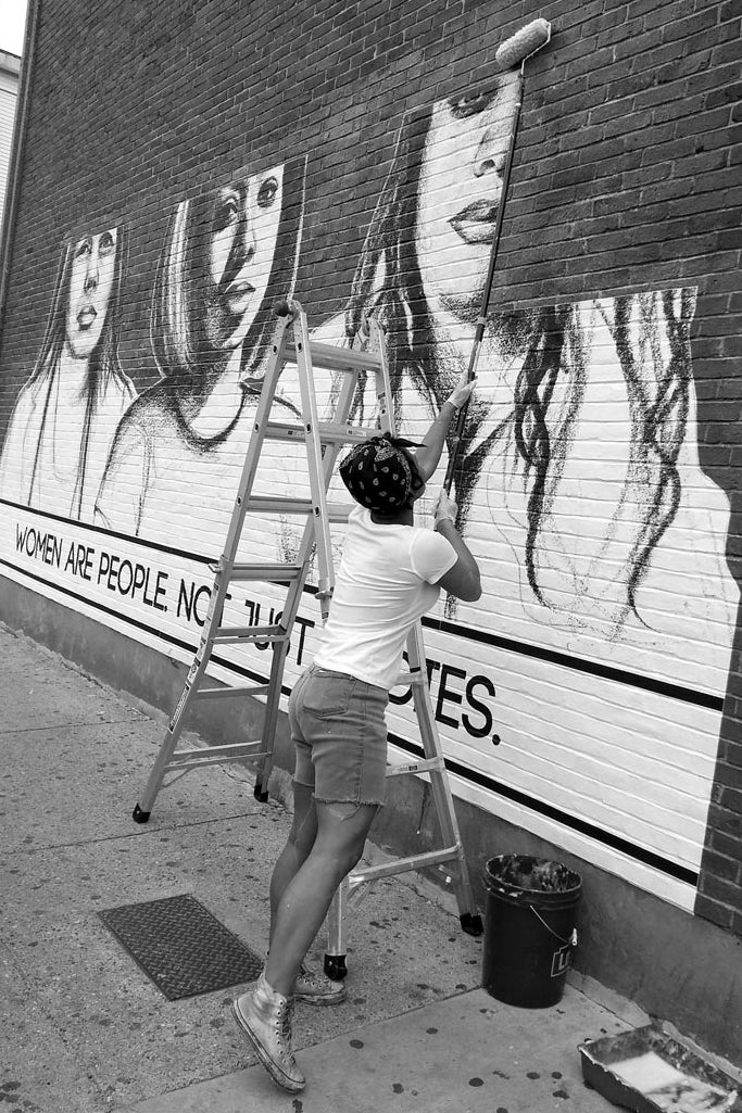 A woman pastes posters on a wall. They feature drawings of women along with their messages to street harassers.