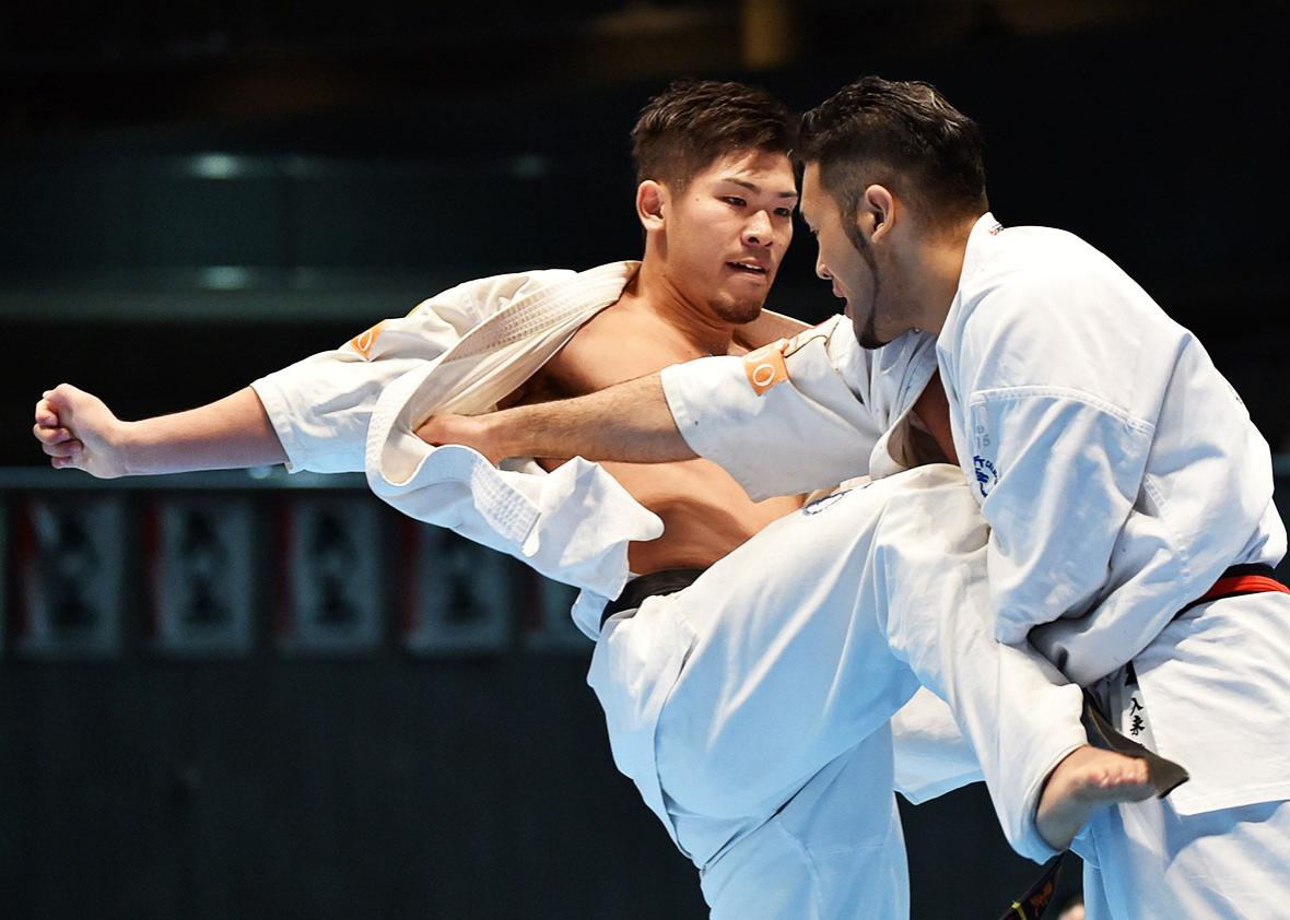 Japan's Yuji Shimamoto (L) and his compatriot Kembu Iriki (R) fight during the men's final match of the 11th World Karate Championship in Tokyo on November 1, 2015.