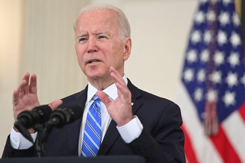 Biden speaking into a mic and standing in front of a US flag