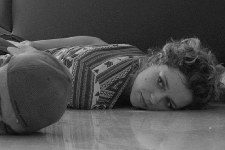 A black-and-white photo of a woman lying on the ground with her face to a tile floor.