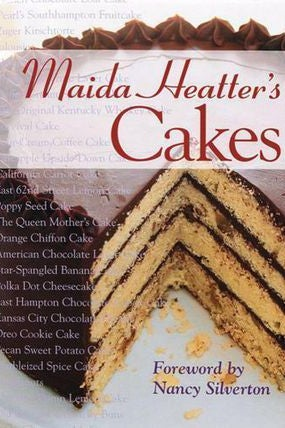 A book cover with a yellow layer cake with chocolate frosting. Maida Heatter's Cakes, foreword by Nancy Silverton.