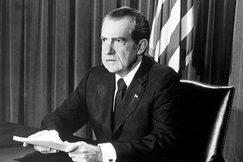 Richard Nixon sits at a desk.