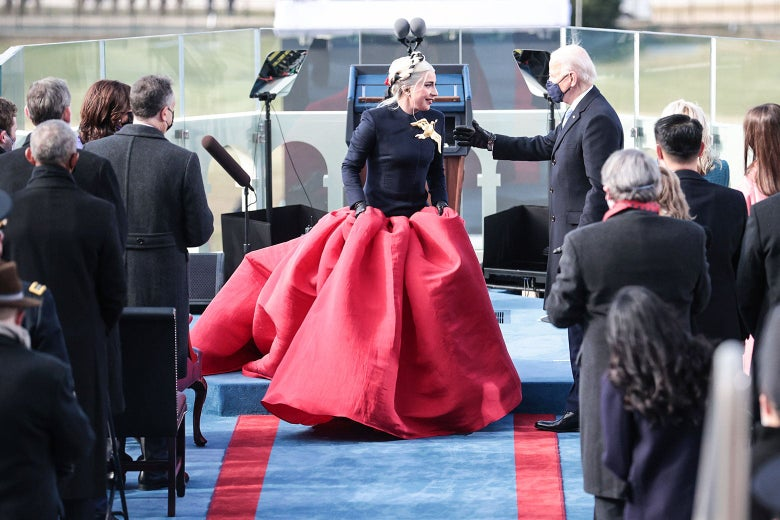 Lady Gaga talks to Joe Biden. She is wearing a voluminous red skirt with a close-fitting navy top, topped with a large gold bird pin.