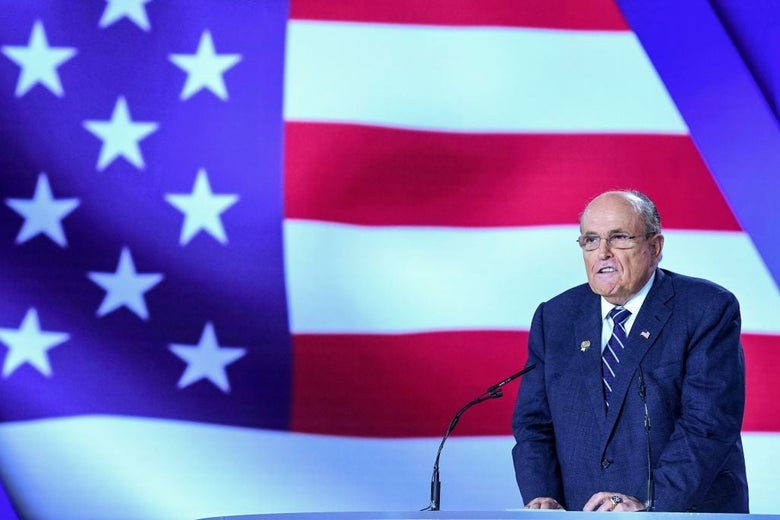 Giuliani, wearing a blue suit, speaks at a lectern in front of a large screen displaying an image of the American flag.