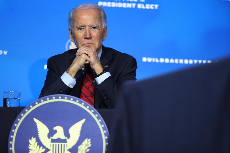 Biden sits with his elbows on a table and his hands clasped, with a presidential seal in front of him