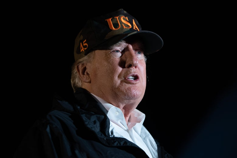 """President Trump, wearing a windbreaker and camo ball cap that says """"USA,"""" speaks. It is night."""