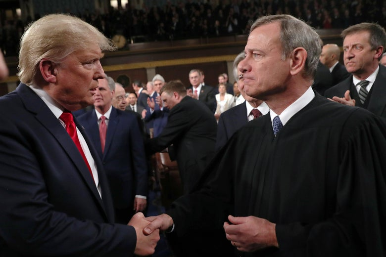 Donald Trump locks eyes with John Roberts as the two men shake hands.