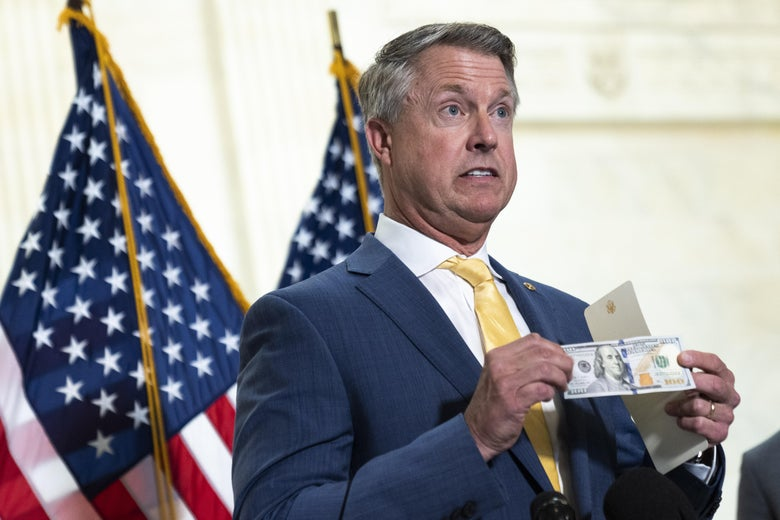Roger Marshall holds up a $100 bill while standing in front of two U.S. flags.