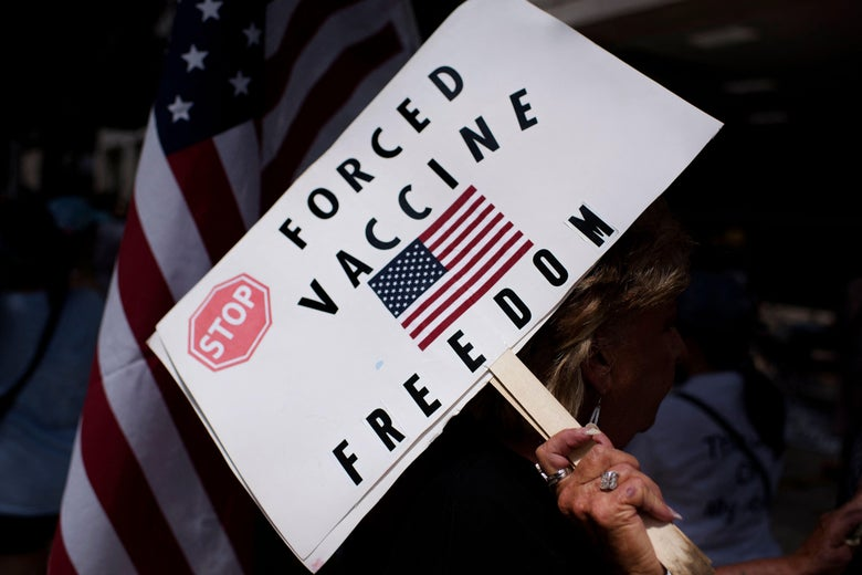 """A sign featuring a U.S. flag and reading """"Stop Forced Vaccine. Freedom."""""""