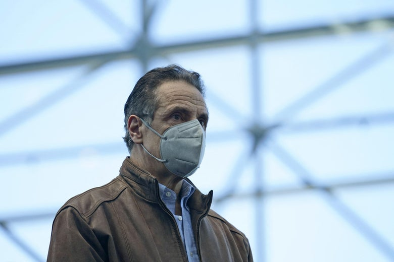 Cuomo stands wearing a gray mask and a brown leather jacket