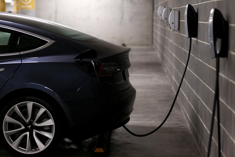 An electric car is seen plugged into an outlet on a brick wall.
