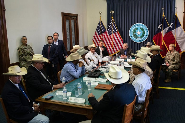 Abbott is seated in a cramped room at the end of a table of men wearing cowboy hats. He himself is not wearing a hat, though.