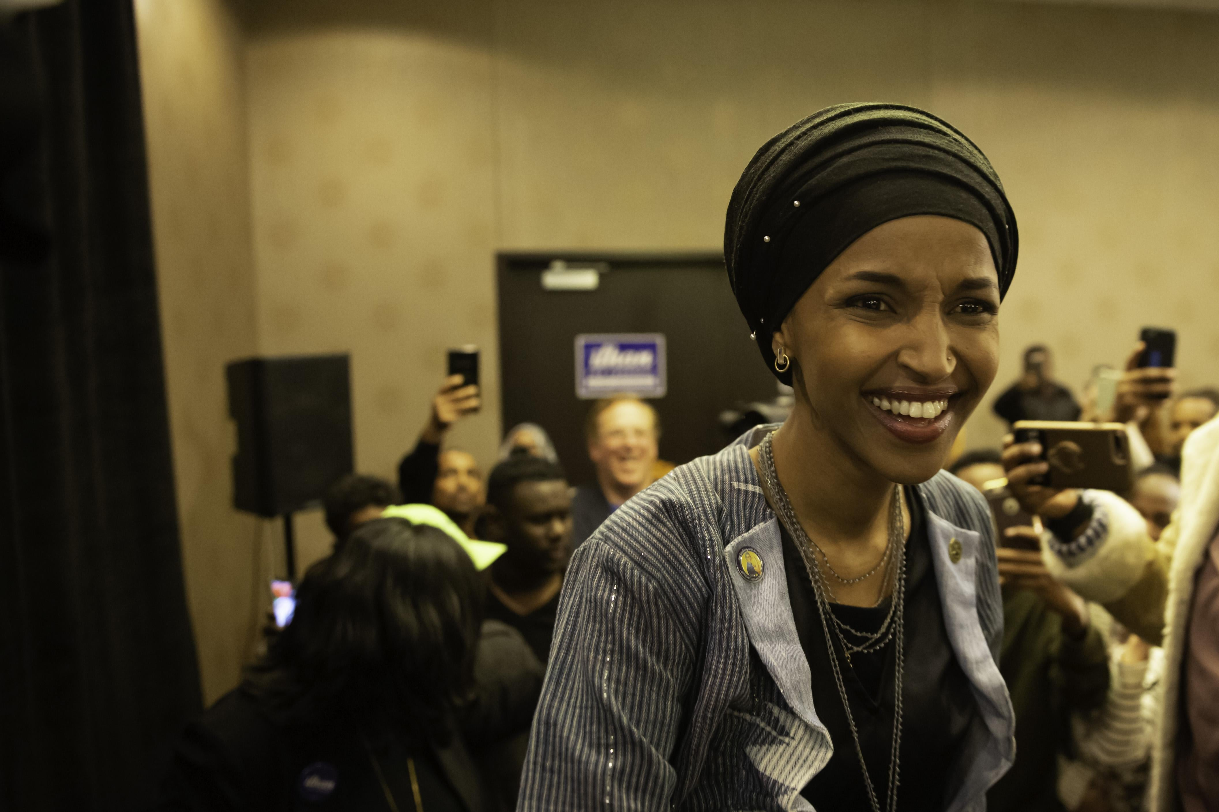 Ilhan Omar smiling, with a crowd behind her.