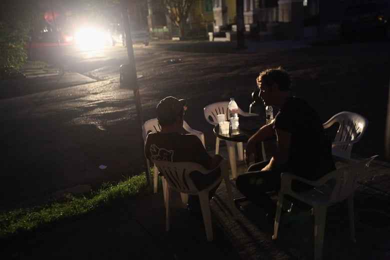 NEW ORLEANS, LA - AUGUST 31:  People chat outside a bar during a continued blackout on August 31, 2012 in the Bywater neighborhood of New Orleans, Louisiana. The area was still without electricity three days after Hurricane Isaac knocked out power to hundreds of thousands of people.  (Photo by John Moore/Getty Images)